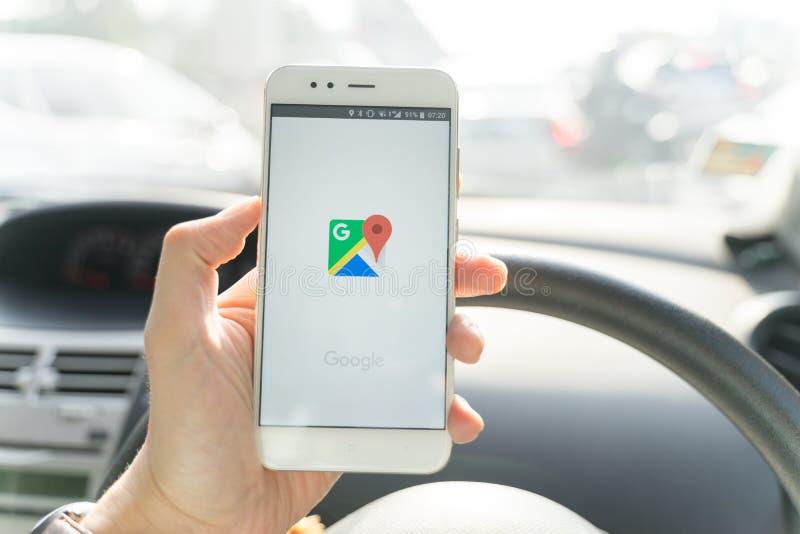 BANGKOK, THAILAND - 08 OCTOBER 2018:Close up of man holding new xiaomi smartphone and Launching Google Maps app. royalty free stock photos