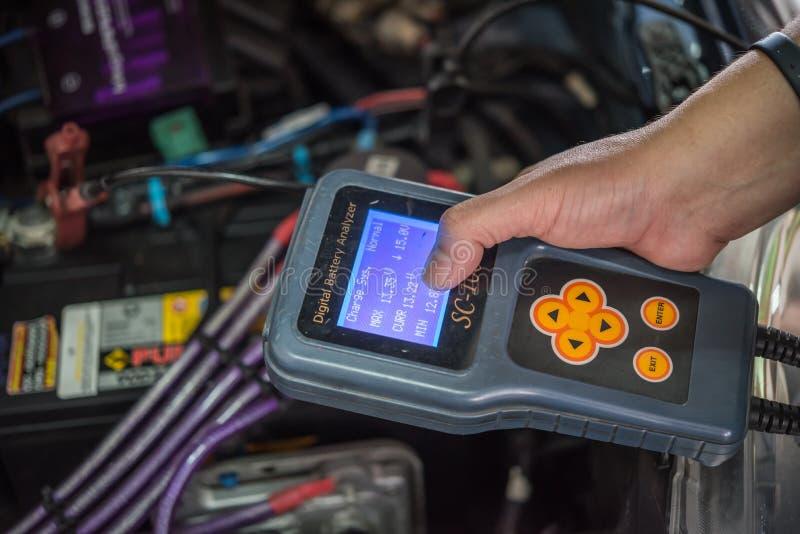 Checking a car battery for repair at car garage. Bangkok, Thailand - October 7, 2017 : Unidentified car mechanic or serviceman checking a car battery by Digital stock photography