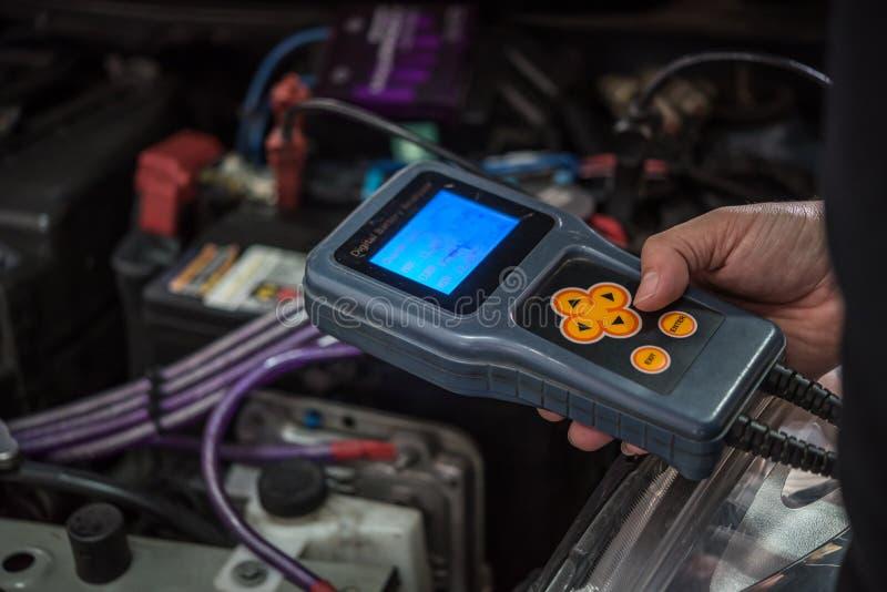 Checking a car battery for repair at car garage. Bangkok, Thailand - October 7, 2017 : Unidentified car mechanic or serviceman checking a car battery by Digital royalty free stock photo