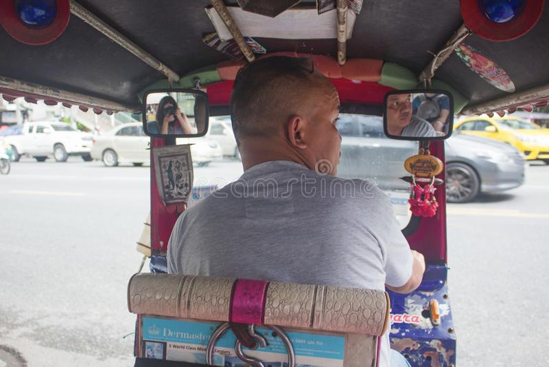 Bangkok Thailand - Oktober 2017: Beskåda från inre en Tuk Tuk i upptagna gator av Bangkok med den unga thailändska chauffören arkivfoto