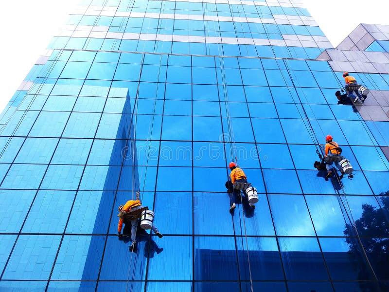 Bangkok Thailand - Oktober 16, 2017: Grupp av mer ren hänga, tvätt- och rengörafönster på hög löneförhöjningbyggnad arkivbilder