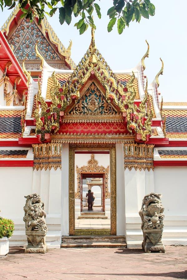 Bangkok Thailand - Oktober 2017: Lejonstatyer som bevakar dörröppningen till den Wat Pho templet, med par i avståndet royaltyfri fotografi