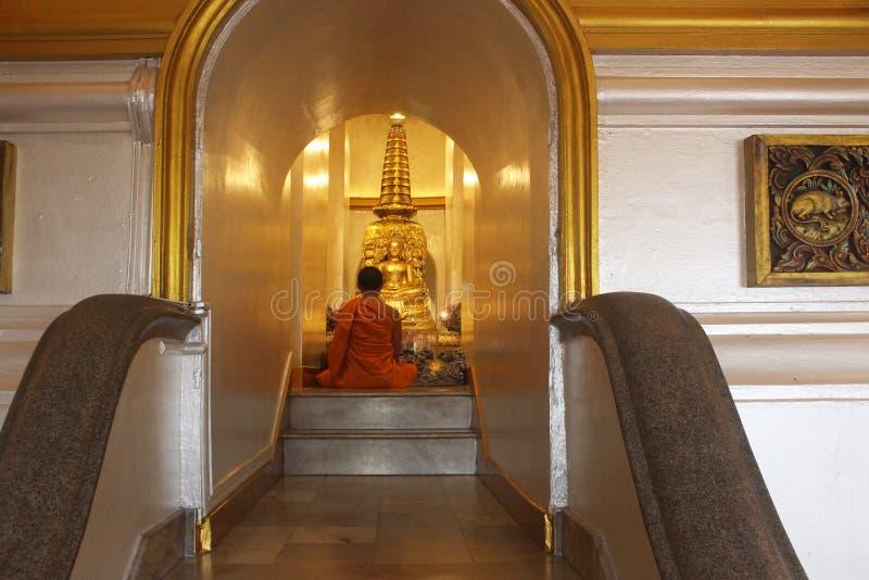 Bangkok Thailand - Oktober 2017: Munk som framme sitter och ber av den Buddah statyn inom Wat Saket eller guld- montering royaltyfri bild