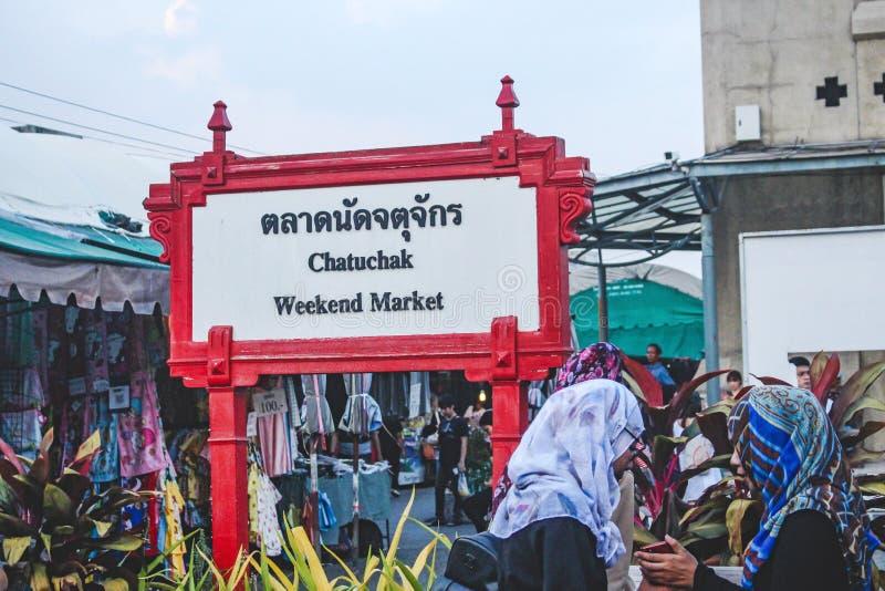 BANGKOK THAILAND - Oktober 2017: Tecken av Jatujak eller den Chatuchak marknaden i Bangkok Två thailändska kvinnor som bär sjalet arkivbild