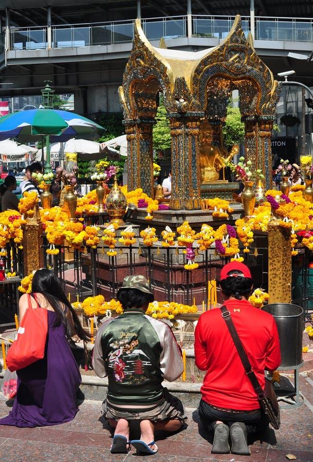 Bangkok, Thailand: Pepple Praying at Erawan Shrine. Thais kneeling in prayer at the flower-covered Thao Maha Brahma, popularly known as the Erawan Shrine in stock photos