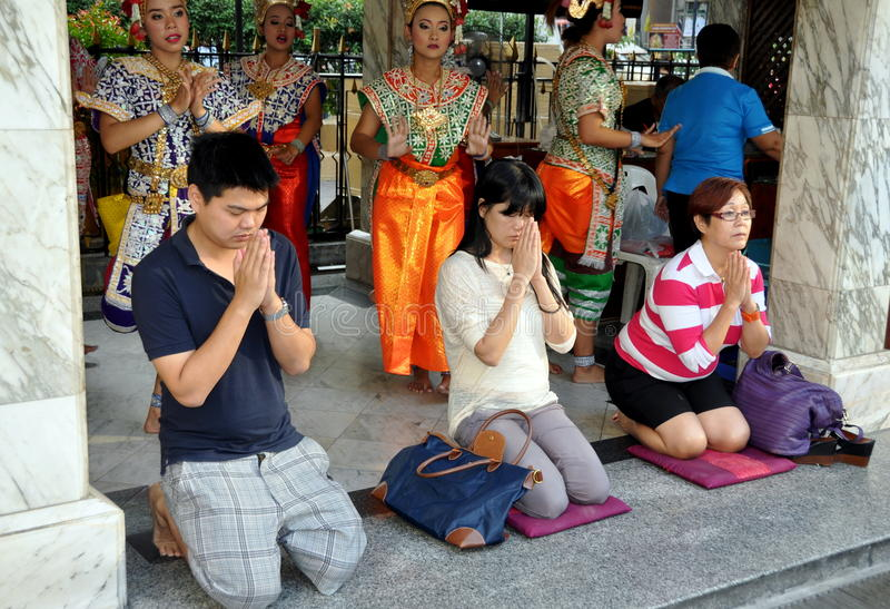 Bangkok, Thailand: Praying at Erawan Shrine. Thai people, their hands clasped in prayer, kneel on fabric mats in front of the dancing pavilion at the holy Erawan stock photo