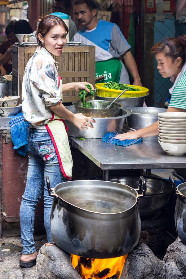 Young girl working in street kitchen stock photo