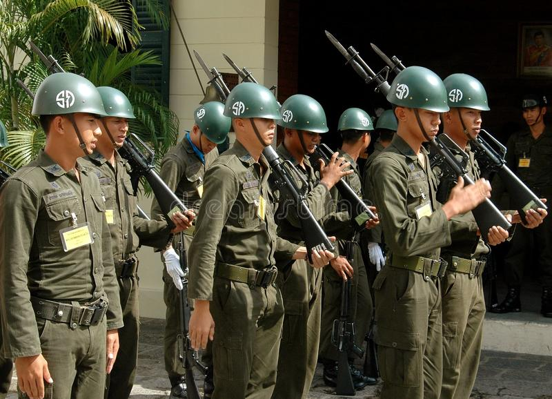 Bangkok, Thailand: Soldiers at Royal Palace. A small group of Thai military soldiers with helmets, rifles and bayonets standing at attention at the Royal Palace royalty free stock photography