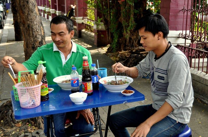Bangkok Thailand: Thailändska män som äter på trottoarrestaurangen royaltyfri bild