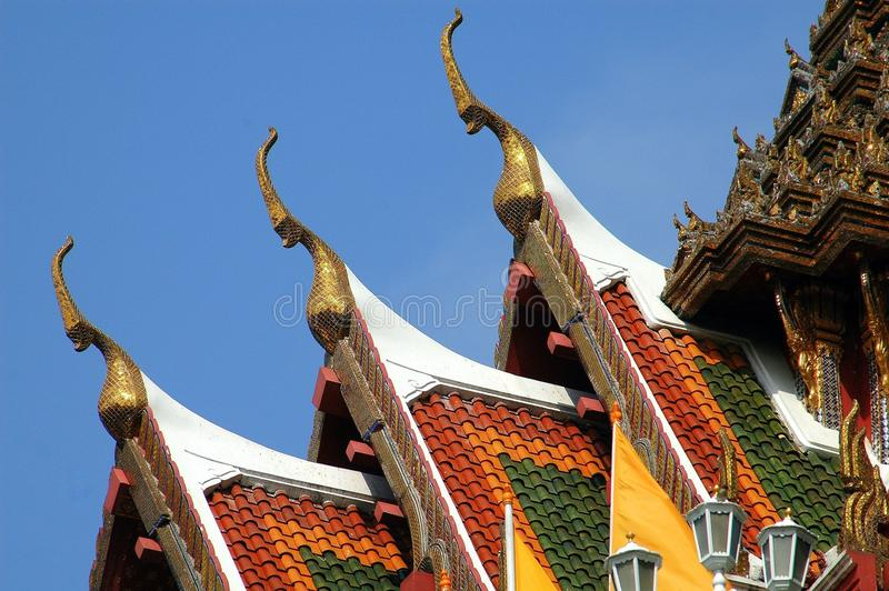 Bangkok, Thailand: Wat Yannawa Chofahs. Steeply gabled roofs with orange, green, and yellow tiles and large gilded bird-like chofah ornaments at Wat (Temple) royalty free stock photography