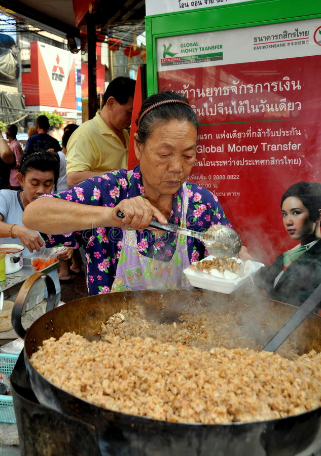 Bangkok, Thailand: Woman Serving Food. Woman worker dishes out a popular Thai dish of chopped pork from a huge wok at a small outdoor restaurant on Thanon royalty free stock image