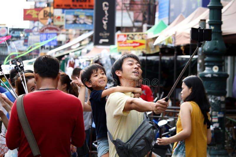 BANGKOK, THAILANS- 3 JUNI 2018: Vader die zijn zoon op rug vervoeren die beeld nemen door smartphone op selfiestok en in Khao wan stock foto