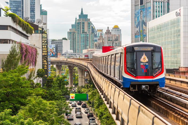 Bangkok: a train leaves Nana BTS station, with a view of modern downtown buildings and Sukhumvit Road royalty free stock photography