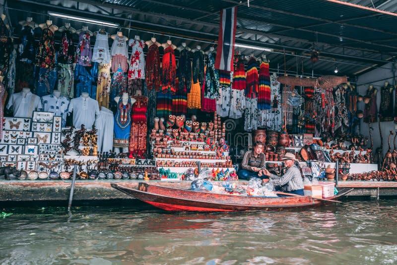 Bangkok, 12 11 18: Twee Verkopersbespreking aan elkaar en exchangig goederen Saduak het drijven markt buiten Bangkok stock afbeeldingen