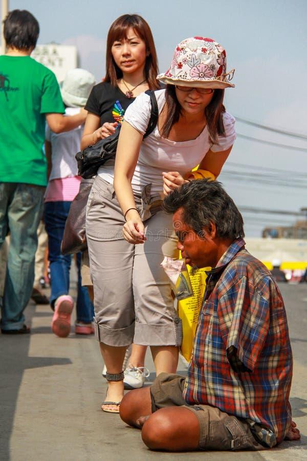 Bangkok - 2010: Una mujer buena que da el dinero a un indigente imágenes de archivo libres de regalías