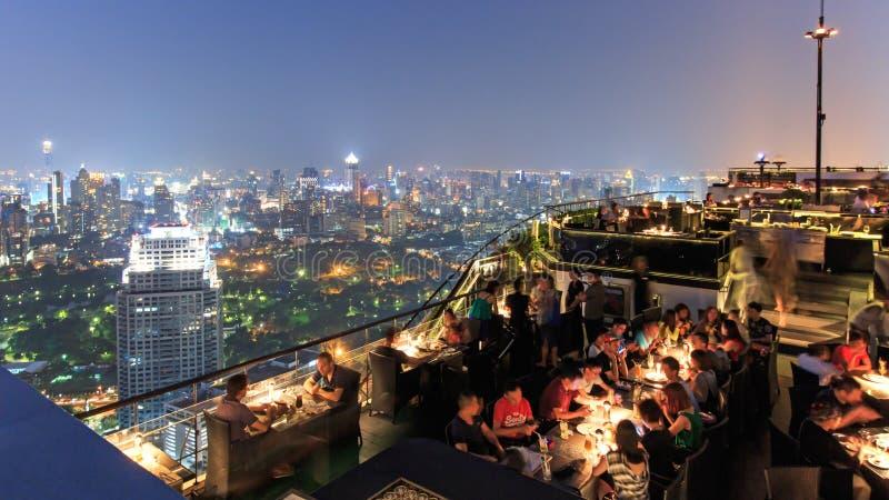 Bangkok vid natten som beskådas från en taköverkantstång med många turister som tycker om platsen royaltyfri foto