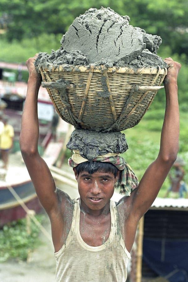 Bangladeschische Arbeitskraft entladen Schiff mit Frachtsand stockfotos