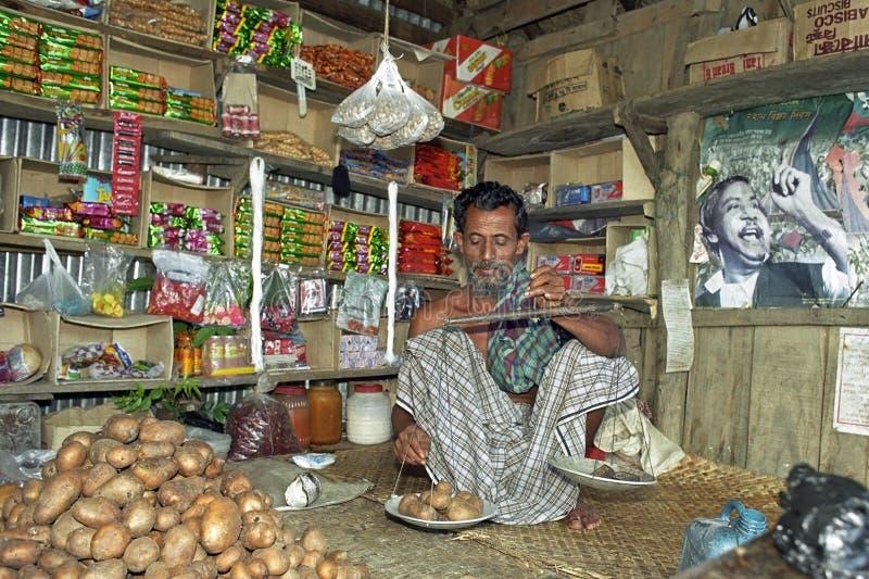 Bangladeschischer Lebensmittelhändler wiegt Kartoffeln in seinem Shop lizenzfreie stockfotos