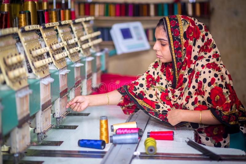Bangladesh - 6 de agosto de 2019: Uma trabalhadora de vestuário de mulheres bangladeshi que trabalha com a Máquina de Bordados Co foto de stock royalty free