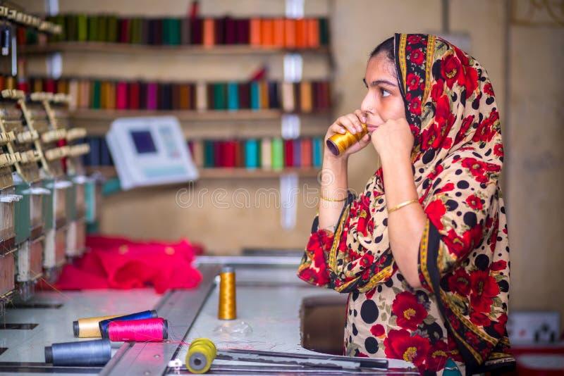 Bangladesh - 6 de agosto de 2019: Uma trabalhadora de vestuário de mulheres bangladeshi que trabalha com a Máquina de Bordados Co fotografia de stock royalty free