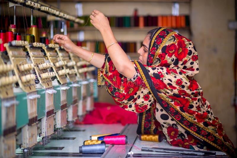 Bangladesh - 6 de agosto de 2019: Uma trabalhadora de vestuário de mulheres bangladeshi que trabalha com a Máquina de Bordados Co imagens de stock
