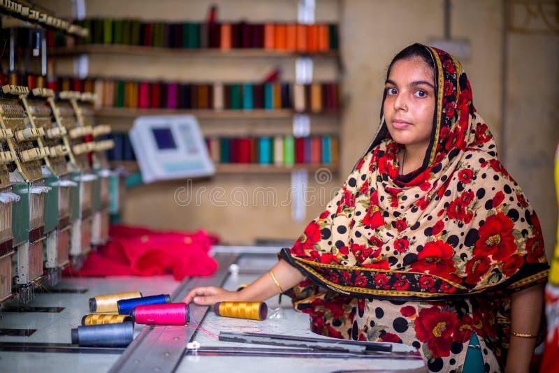 Bangladesh - 6 de agosto de 2019: Uma trabalhadora de vestuário de mulheres bangladeshi que trabalha com a Máquina de Bordados Co foto de stock