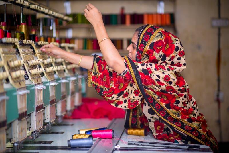 Bangladesh - 6 de agosto de 2019: Uma trabalhadora de vestuário de mulheres bangladeshi que trabalha com a Máquina de Bordados Co fotos de stock