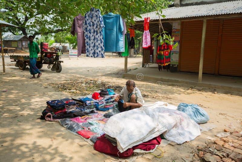 Bangladesh - 19 de mayo de 2019: Un empresario de aldea rural que vende tela y productos para colgar en el tronco del árbol, Mehe foto de archivo libre de regalías