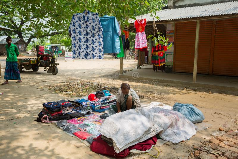Bangladesh - 19 de mayo de 2019: Un empresario de aldea rural que vende tela y productos para colgar en el tronco del árbol, Mehe fotos de archivo