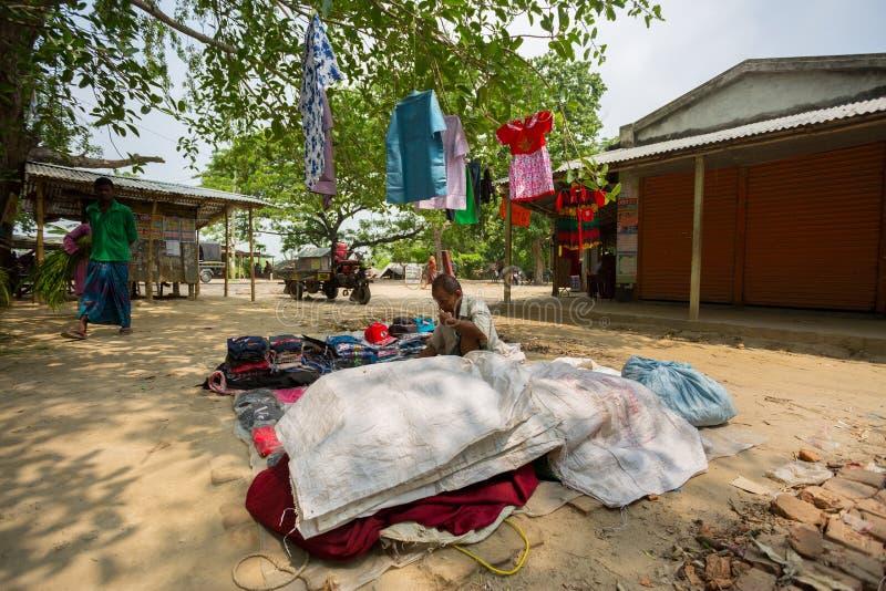 Bangladesh - 19 de mayo de 2019: Un empresario de aldea rural que vende tela y productos para colgar en el tronco del árbol, Mehe fotografía de archivo