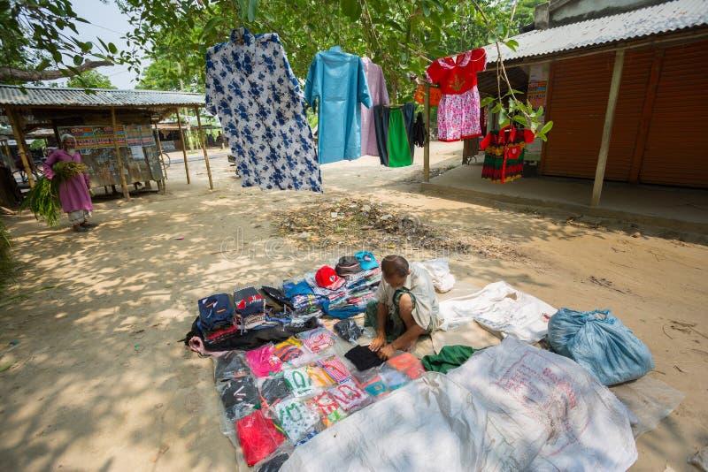 Bangladesh - 19 de mayo de 2019: Un empresario de aldea rural que vende tela y productos para colgar en el tronco del árbol, Mehe fotos de archivo libres de regalías