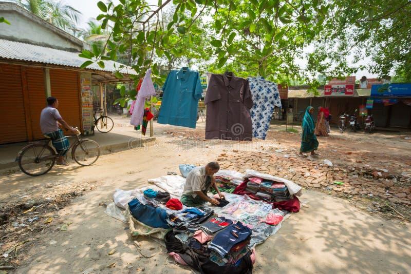 Bangladesh - 19 de mayo de 2019: Un empresario de aldea rural que vende tela y productos para colgar en el tronco del árbol, Mehe imagen de archivo