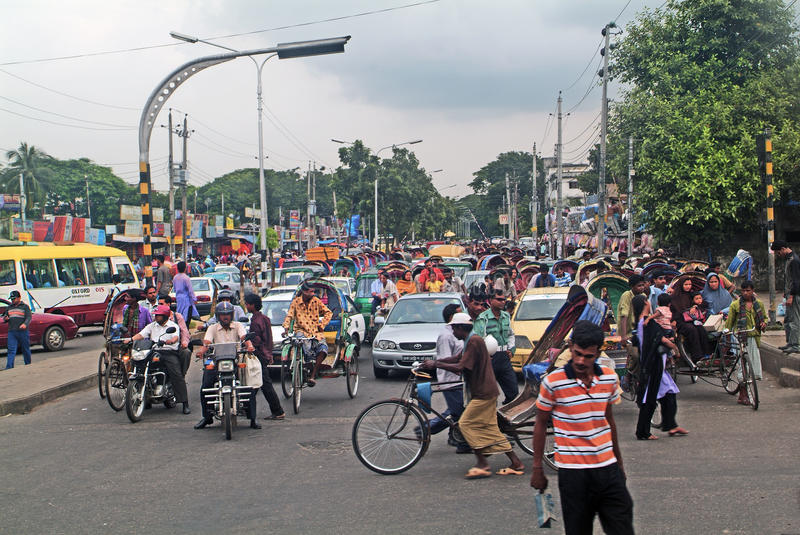 Bangladesh, Dhaka,. Dhaka, Bangladesh - September 17th 2007: Unidentified people on road with car, bikes and rickshaws, usual traffic in the capital stock images