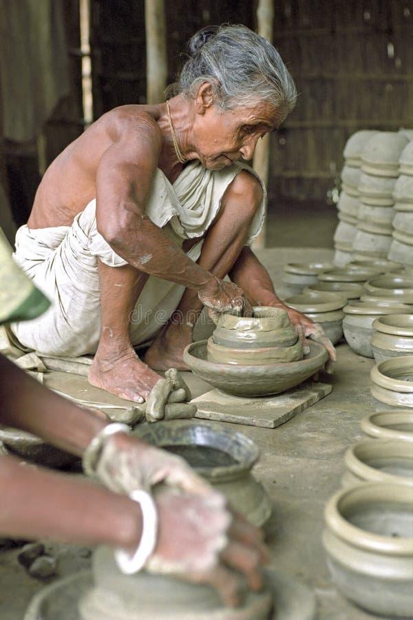 Bangladeshi senior potter at work in pottery stock photography