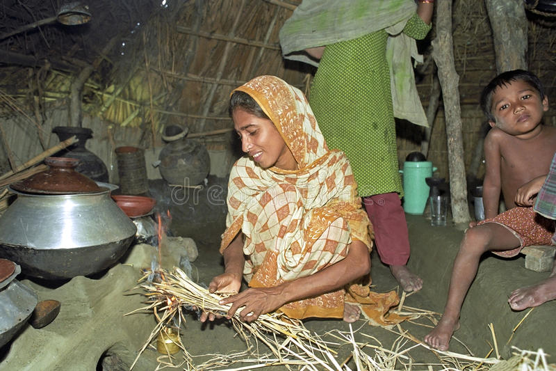 Bangladeshi woman during cooking in primitive hut. Bangladesh, Charburhan village on the island Charkajal, Bay of Bengal, a Bengali woman in colorful traditional royalty free stock photography