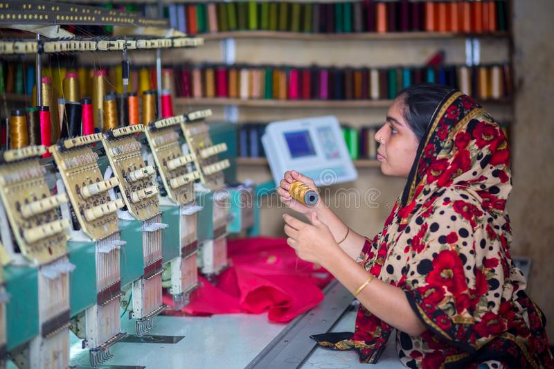 Bangladesh – August 6, 2019: A Bangladeshi woman garments worker working with Computerized Embroidery Machine at Madhabdi, stock photos