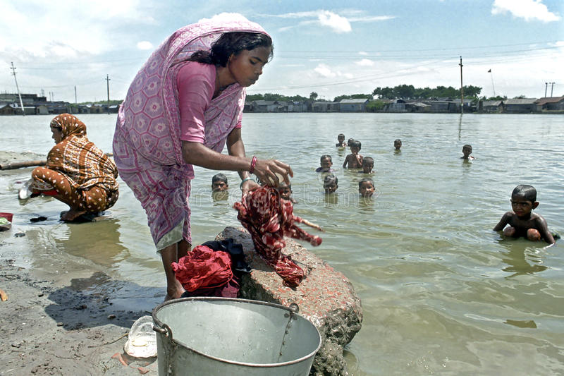 Bangladeshi woman washing clothes in lake. Bangladesh: City view of the capital Dhaka: Women washing clothes, while children bathe or swim in the polluted lake stock image
