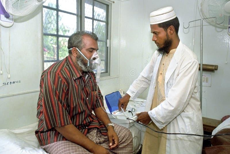 Bangladeshisk doktor som arbetar i sjukhus med patienten arkivbild