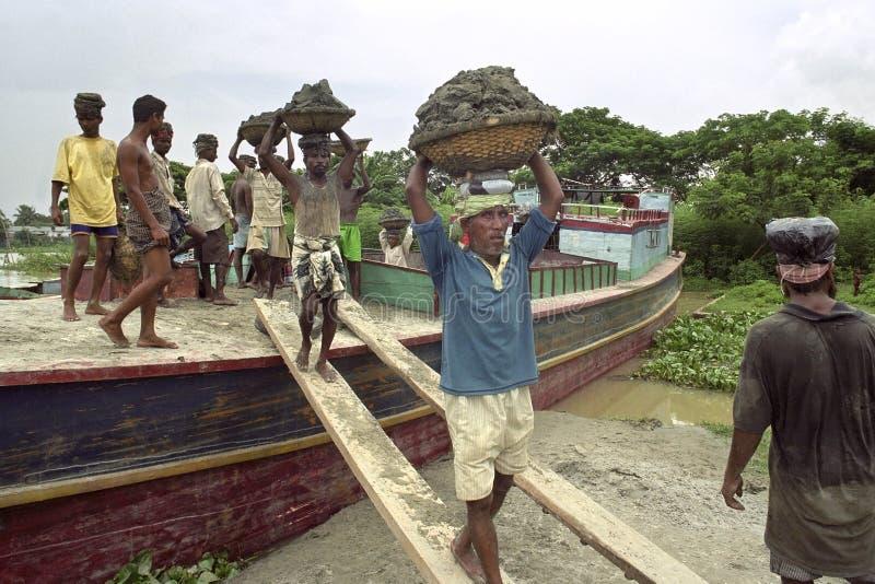Bangladeshiska arbetare lastar av fraktbåten med lastsand arkivfoto