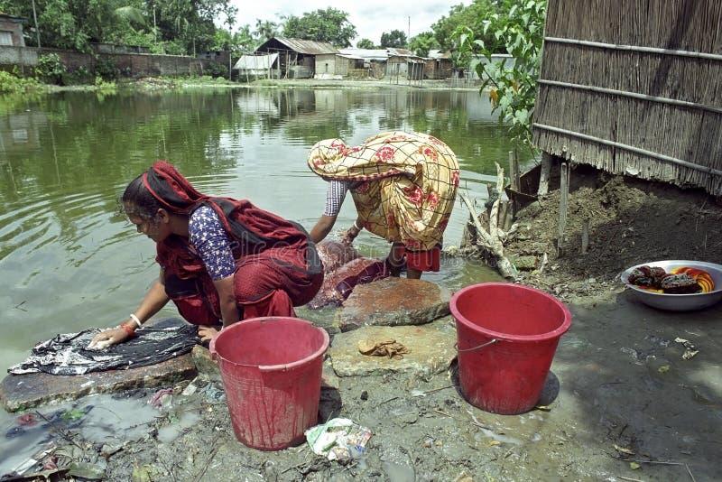 Bangladeshiska kvinnor som tvättar kläder i en sjö royaltyfri fotografi