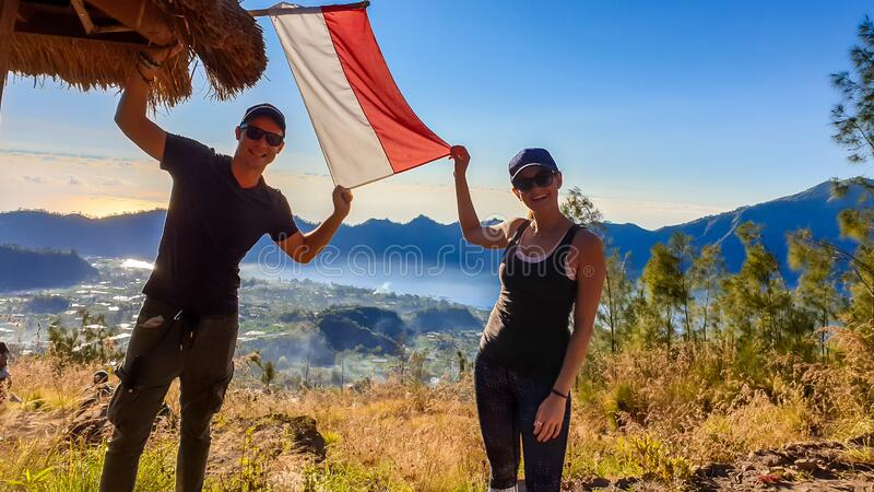 Bangli - A couple on top of Mt Batur holding Indonesian flag. A couple in sporty outfit standing on top of Mount Batur and holding an Indonesian flag in their stock image