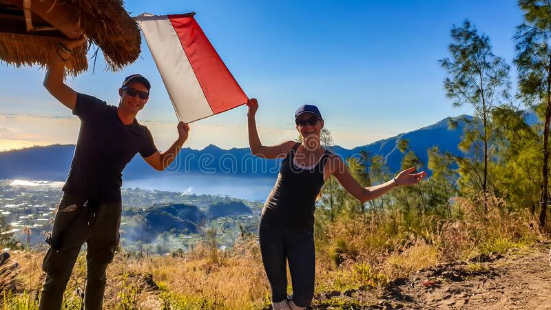 Bangli - A couple on top of Mt Batur holding Indonesian flag. A couple in sporty outfit standing on top of Mount Batur and holding an Indonesian flag in their royalty free stock images