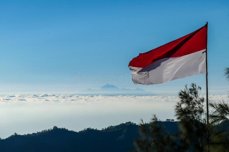 Bangli - An Indonesian flag waving with Mt Rinjani over the horizon line. An Indonesian flag waving with the wind seen from the top of Mount Batur. There is Mt royalty free stock images