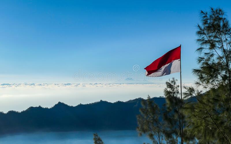 Bangli - An Indonesian flag waving with Mt Rinjani over the horizon line. An Indonesian flag waving with the wind seen from the top of Mount Batur. There is Mt royalty free stock photo