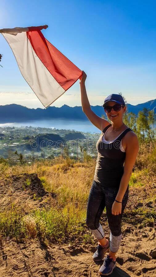 Bangli - A woman on top of Mt Batur holding Indonesian flag. Woman in sporty outfit standing on top of Mount Batur and holding an Indonesian flag in her hand stock image