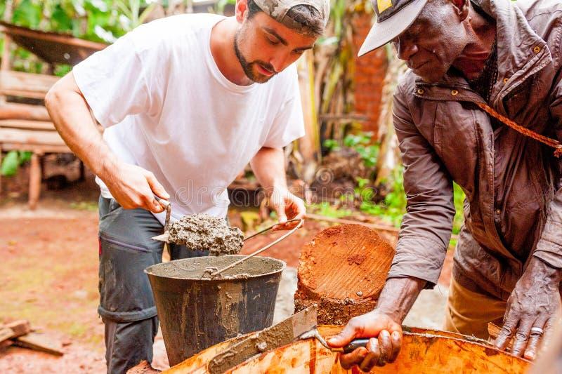 Bangoua,喀麦隆- 08威严2018年:年轻欧洲人在做手工作品大厦与混凝土的非洲村庄水井 库存照片