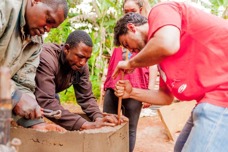 Bangoua, Kamerun - 8. August 2018: junger europäischer Freiwilliger im afrikanischen Dorfgebäude-Wasserbrunnen mit Spachtel und B stockbild