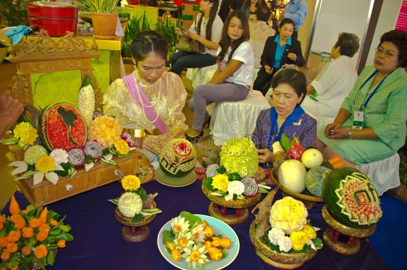 BANGUECOQUE - 3 de agosto: As mulheres tailandesas estão cinzelando frutos em Tailândia fotografia de stock