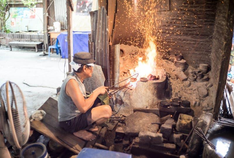 Banguecoque - junho 5,2017: O homem marcava a bacia ou o almsbowl do ` s da monge na comunidade de Bronzework dos Bu de Baan imagem de stock