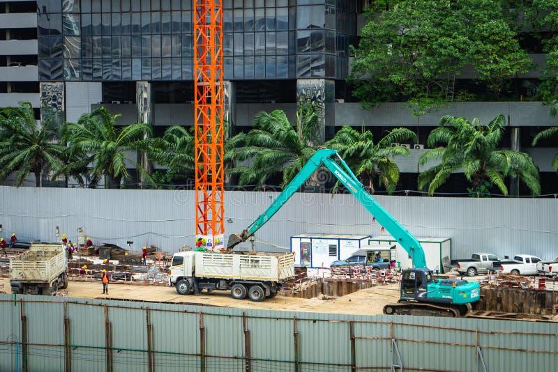 Banguecoque - Tailândia, 29 2018: Carga do trabalhador e da máquina escavadora do construtor fotografia de stock